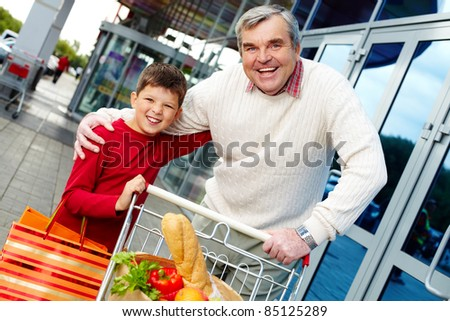Portrait of grandfather and grandson with goods near supermarket