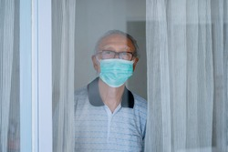 Portrait of grandfather looking through the window while wearing facial mask and doing self isolation