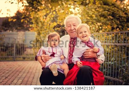 Portrait of grandparents with grandchildren in Ukrainian costume at sunset