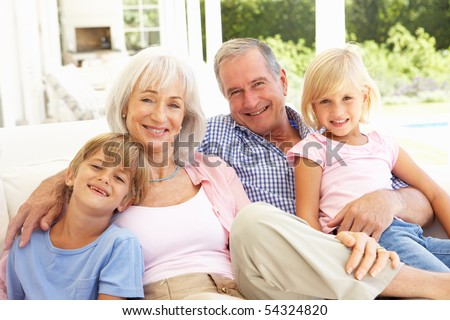 Portrait Of Grandparents With Grandchildren Relaxing Together On Sofa