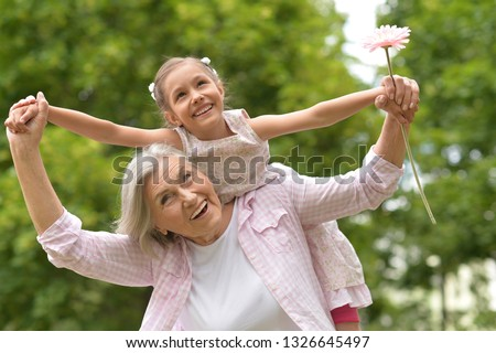 Portrait of granny and granddaughter posing outdoors