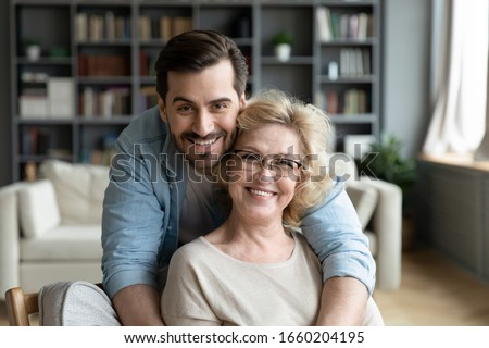 Portrait of grateful adult man hug smiling middle-aged mother show love and care, thankful happy grown-up son in embrace senior 70s mom, enjoy weekend family time at home together, bonding concept