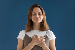 Portrait of grateful hopeful woman holding hands on chest isolated on blue studio background, pleased young female with closed eyes feeling love, gratitude, appreciation, thanking fate