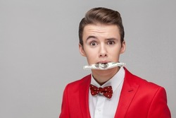 Portrait of greedy businessman with stylish hairdo in red tuxedo and bow tie holding dollar banknote with teeth, looking shocked amazed, money-hungry concept. studio shot isolated on gray background