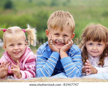 portrait of  group of children happily laughing and lying on the grass - stock photo