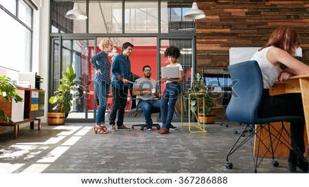 Portrait of group of creative people having a meeting with a laptop in a modern office. Business people having relaxed conversation over new project.