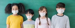 Portrait of group of international students wearing face mask, self-protection from corona virus pandemic. New normal children lifestyle, back to school banner