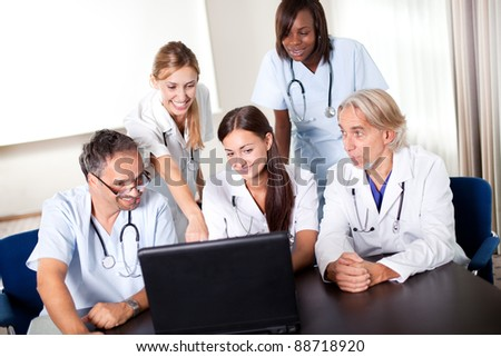 Portrait of group of smiling hospital colleagues looking at the laptop and discussing
