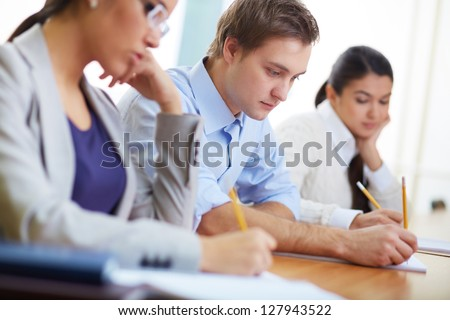 Portrait of group of students making notes or writing test