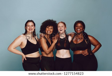 Photo of  Portrait of group of women posing together in sportswear against a gray background. Multiracial females with different size standing together looking at camera and smiling.