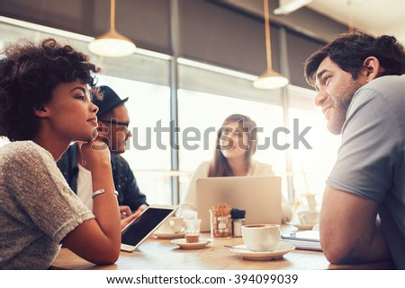 Portrait of group of young people sitting at a cafe and discussing work. Young men and women at coffee shop for startup meeting.