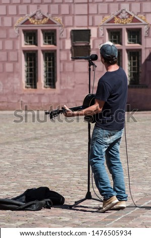 Portrait of guitarist playing on cobbles place in Mulhouse