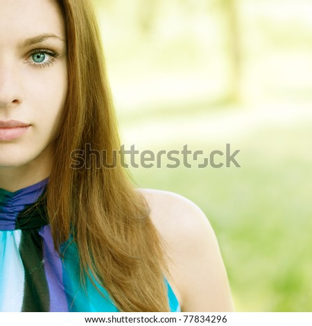 portrait of half face beautiful young woman on green background