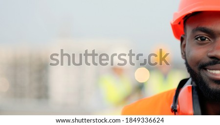 Portrait of half face of handsome African American young man in casque and headphones looking at camera at construction site and smiling. Close up of happy male builder at building. Constructing. Stock photo ©