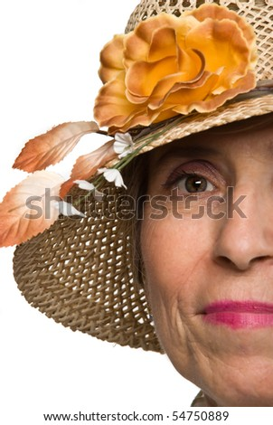 Portrait of half face of senior woman with green eyes wearing a hat with flowers isolated on white background