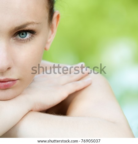 portrait of half face young woman on green background