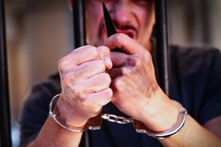 Portrait of handcuffed man with a knife imprisoned for crime, punished for serious villainy. Arrest, gangster, pain concept.