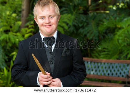 Portrait of handicapped drummer boy in black suit outdoors.