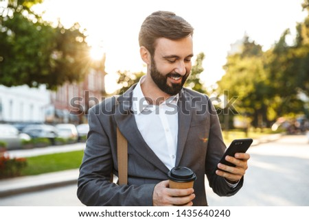 Portrait of handsome adult businessman in formal suit holding takeaway coffee and using smartphone while walking through city street #1435640240