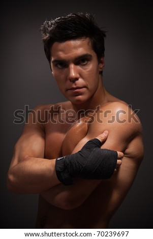 Portrait of handsome adult man with big muscles on dark background