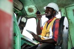 Portrait of handsome Africa American engineering using walkie talkie for control labor in train driver's room. Mechanical control in historical locomotive.