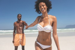 Portrait of handsome African-American man holding hand of beautiful mixed-race woman at beach on a sunny day. They are smiling and looking at camera