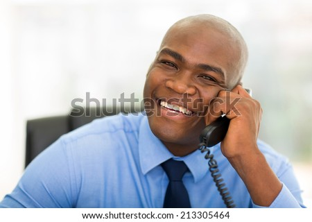 portrait of handsome african office worker talking on telephone