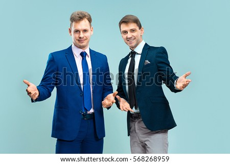 Portrait of handsome and elegant business men wearing necktie and suits on gray studio background