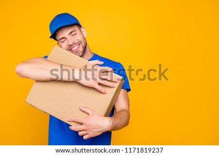 Portrait of handsome attractive cheerful funny funky deliver with stubble in blue uniform holding card-board box, dreaming, embracing box, isolated over bright vivid yellow background, copy-space