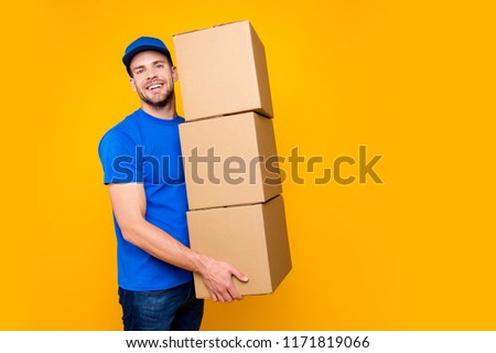 Portrait of handsome attractive funny bearded deliver in blue uniform holding three large heavy big cardboard boxes on-time, isolated over bright vivid yellow background, copy-space