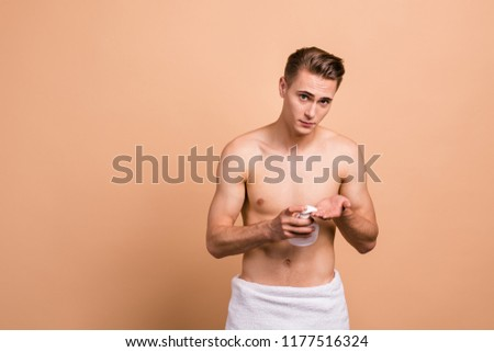 Portrait of handsome, attractive man with towel, naked torso, pushing dispenser of white bottle with soap on hands looking at camera isolated on beige background