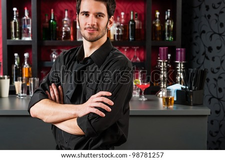 Portrait of handsome barman standing in front of the bar - stock photo