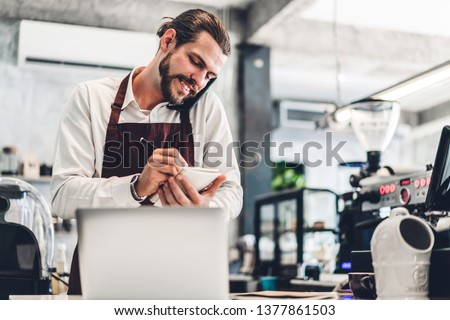 Portrait of handsome bearded barista man small business owner smiling and receive order from customer behind the counter bar in a cafe