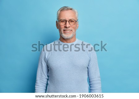 Portrait of handsome bearded European man with grey hair and beard smiles pleasantly looks directly at camera being in good mood has lucky day wears spectacles and sweater isolated over blue wall