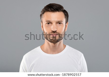 Portrait of handsome bearded man over grey studio background, empty space. Middle-aged bearded man posing for male magazine or blog, youth, healthy lifestyle and male cosmetology concept Photo stock ©