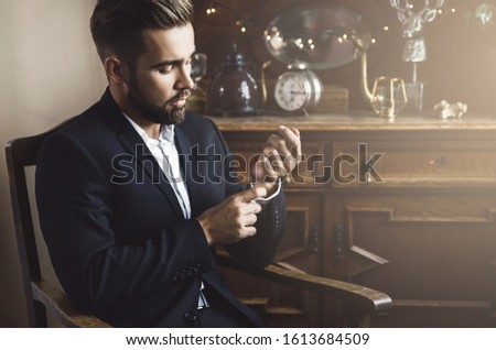 Portrait of handsome bearded man wearing black classic suit
