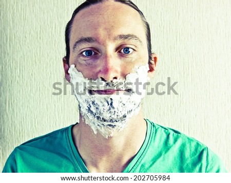 Portrait of handsome bearded young man with shaving foam on face. Image with vintage filter