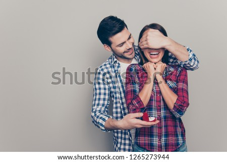 Portrait of handsome beautiful crazy ecstatic laughing lady and positive cheerful glad in casual plaid shirt macho closing face with palm holding small red box with jewellery isolated grey background