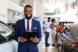 Portrait Of Handsome Black Car Salesman In Suit Posing At Workplace In Auto Showroom, Young Dealership Center Manager With Clipboard In Hands Helping Spouses To Purchase New Automobile, Free Space
