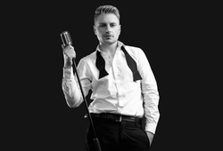 Portrait of handsome blond man singer in elegant tuxedo and bow tie posing with vintage microphone on black studio background