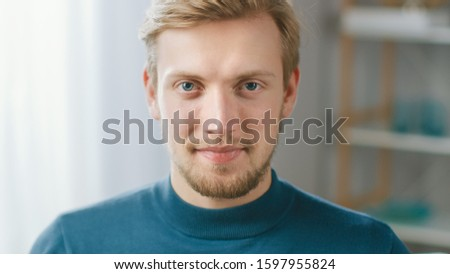 Portrait of Handsome Blonde Young Man Smiling, while Looking at Camera. Happy Attractive Guy with Blue Eyes Foto stock ©