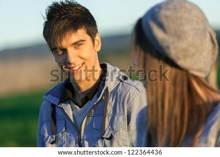 Portrait of handsome boy with girlfriend in countryside.