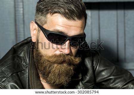 Portrait of handsome brutal unshaved male biker with long beard and moustache in brown leather jacket and black sunglasses sitting on grey wooden background, horizontal picture