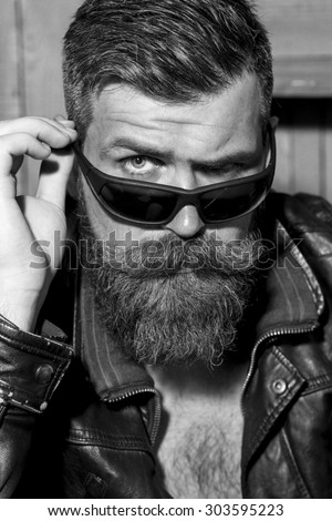 Portrait of handsome brutal unshaved man with long beard and moustache in leather biker jacket and sunglasses looking forward black and white closeup, vertical picture