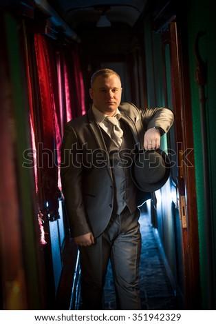 Portrait of handsome businessman in gray suit posing in corridor at retro train #351942329