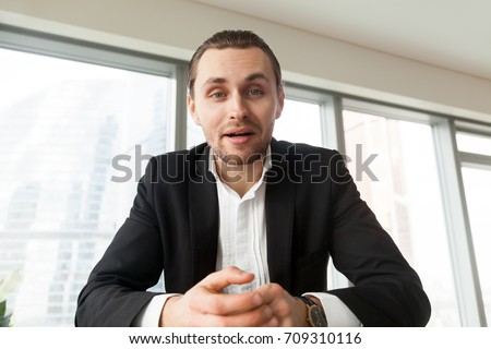 Portrait of handsome businessman looking in camera and talking. Young successful entrepreneur explaining his point to business partners. Business negotiations, boss conducting job interview concept.