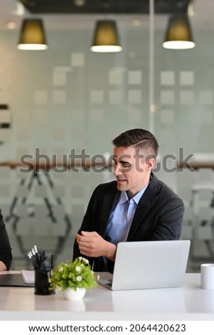 Portrait of handsome businessman or male manager listening her colleagues presenting business plan in conference room.