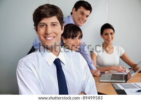 Portrait of handsome businessman smiling with team working in background
