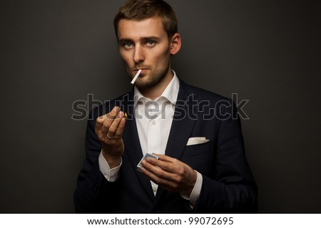 portrait of handsome businessman with cigarette on black