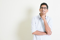 Portrait of handsome casual business Indian man smiling and thinking, eyes looking upwards, standing on plain background with shadow, copy space at side.